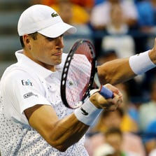 NEW YORK, NY - AUGUST 30:  John Isner of the United States returns a shot against Philipp Kohlschreiber of Germany during men's singles third round match on Day Six of the 2014 US Open at the USTA Billie Jean King National Tennis Center on August 30, 2014 in the Flushing neighborhood of the Queens borough of New York City.  (Photo by Al Bello/Getty Images)