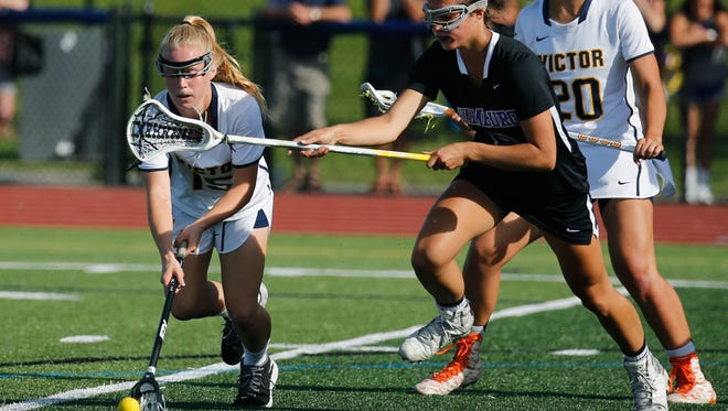 Victor's Kaci Messier picks up the ball under the stick of Hamburg's Bella Lettieri in the first half at Pittsford Sutherland High School.