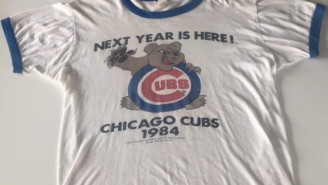"""Tom Baiz, who recently moved from Great Falls to Chicago, and his old shirt have lived through a lot of history to finally see his beloved Cubbies win the World Series. """"Next Year is Here,"""" indeed."""