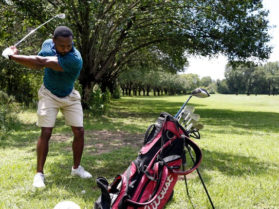 Dunn Johnson, 29, practices his swing at the Grove