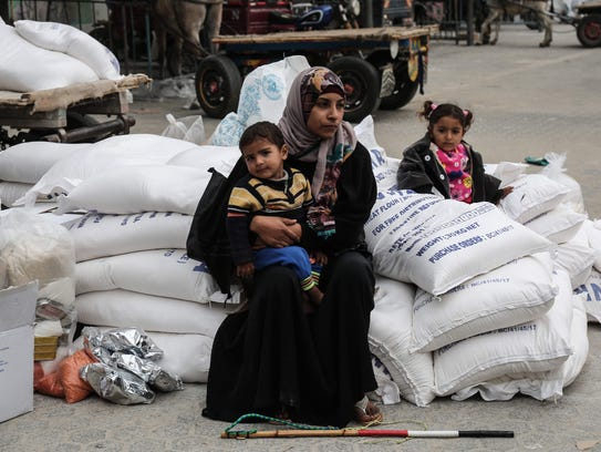 A Palestinian woman sits with a child after receiving