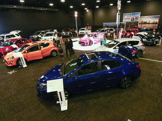 Attendees review vehicles on display in the Toyota