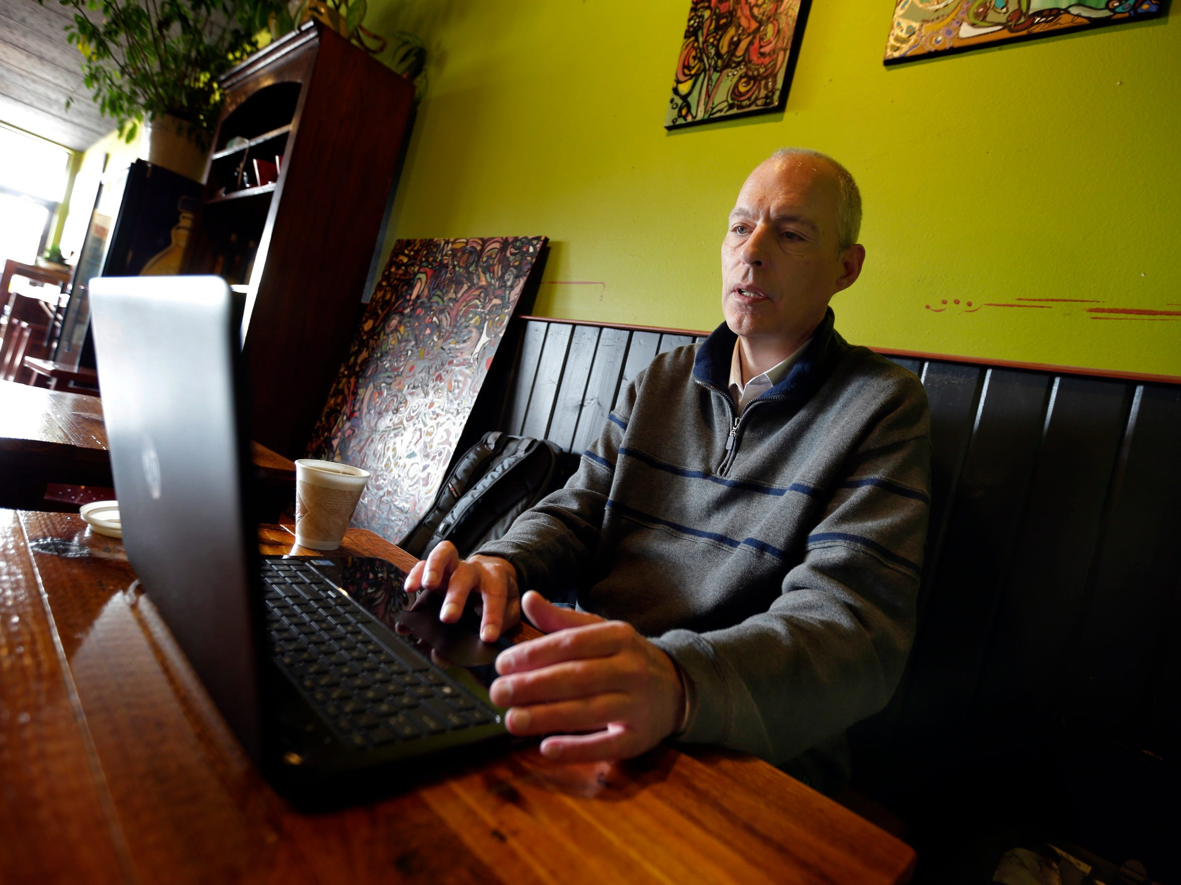 John Schaus works on his computer at a coffee house