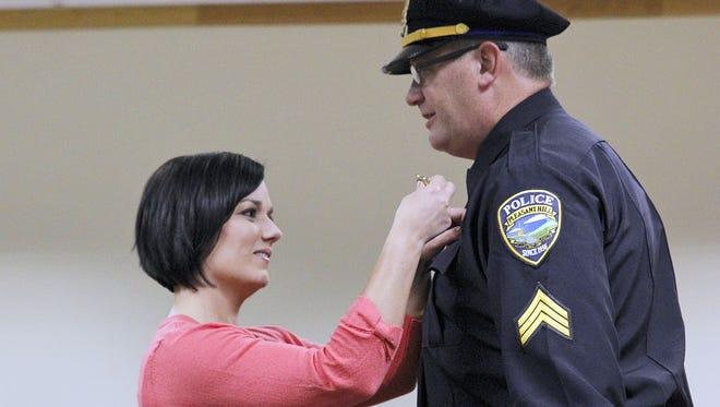 Nikki Killam pins the sergeant badge to her husband Brandon Killam's uniform on March 9, 2016.
