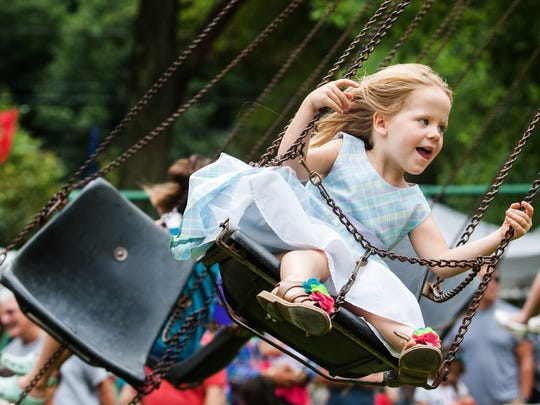 Four year-old Sora Clarke-Fields rides the swing ride at the Arden Fair last year.