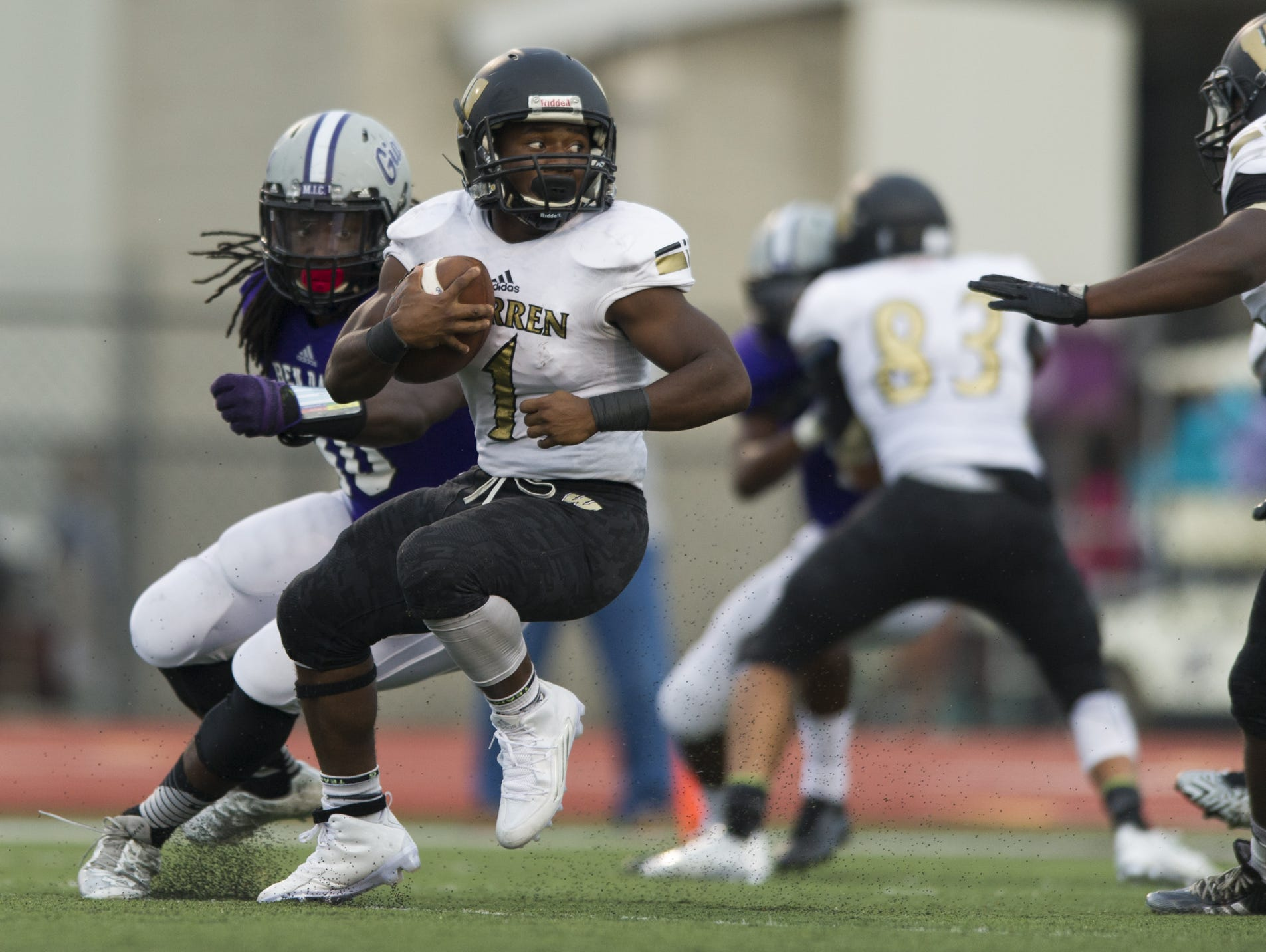 Warren Central High School senior Jaylen Coe (1) changes course in the backfield before being taken down for a loss by the Ben Davis defense during first-half action of a IHSAA varsity football game at Ben Davis High School, Friday, September 18, 2015.