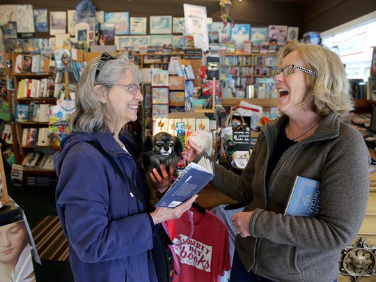Margaret Celestino of Bainbridge Island holds her dog, Muffin, as she talks Thursday with Liberty Bay Books owner Suzanne Droppert in Poulsbo. The store is participating in Saturday's Independent Bookstore Day.