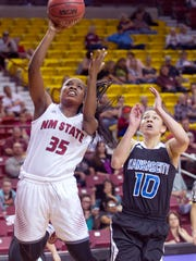New Mexico State's Moriah Mack beats UMKC's Aries Washington to the baseline and puts up a shot Saturday afternoon at the Pan American Center.