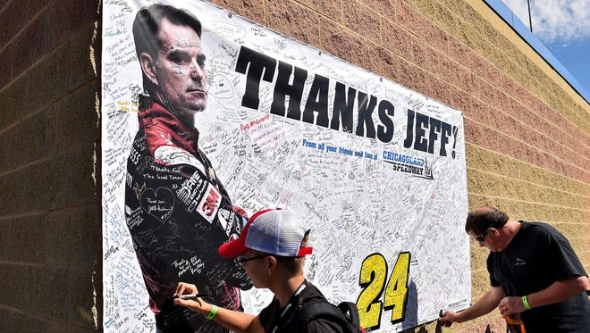 Fans sign a thank you sign for NASCAR Sprint Cup Series driver Jeff Gordon at Chicagoland Speedway.