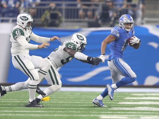 Lions receiver TJ Jones runs by the Jets' Lorenzo Mauldin