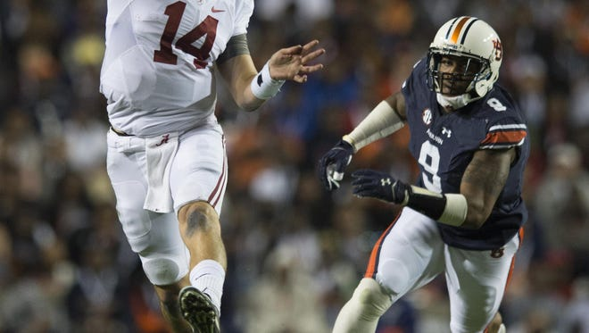 Alabama quarterback Jake Coker (14) throws a touchdown pass as Auburn defensive end Byron Cowart (9) chases him during the second half of the NCAA college football game between Auburn vs. Alabama, Saturday, Nov. 28, 2015, at Jordan-Hare Stadium in Auburn, Ala. Alabama defeated Auburn 29-13.