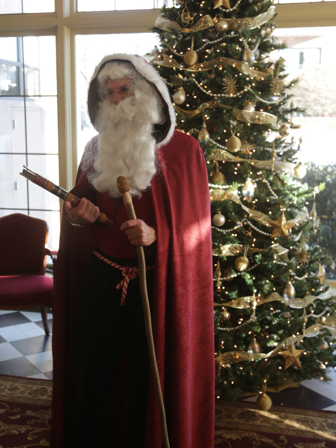 Rick Lohr of the town of Stettin, dressed as Saint Nicholas, interacts with a tour group at the Yawkey House Museum and Marathon County Historical Society tours, Saturday, December 7, 2013, in Wausau.