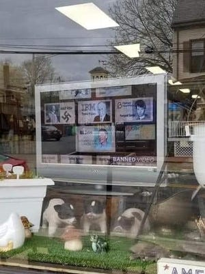 A photo taken of a TV screen displaying images including Adolf Hitler with a swastika, at left, along with other political figures in the storefront of Soups on Main in Hackettstown.