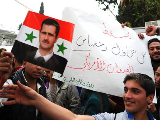 "In this photo released by the Syrian official news agency SANA, pro-government protesters hold a portrait of President Bashar Assad and a placard that reads, ""Down with everyone who cooperated and supported the American aggression,"" during a protest against the U.S. attack on a military airbase last week, in front the the United Nations building, in Damascus, Syria, Tuesday, April 11, 2017. U.S. Secretary of State Rex Tillerson's statement Tuesday, that the reign of Assad's family ""is coming to an end"" suggests Washington is taking a much more aggressive approach about the Syrian leader."