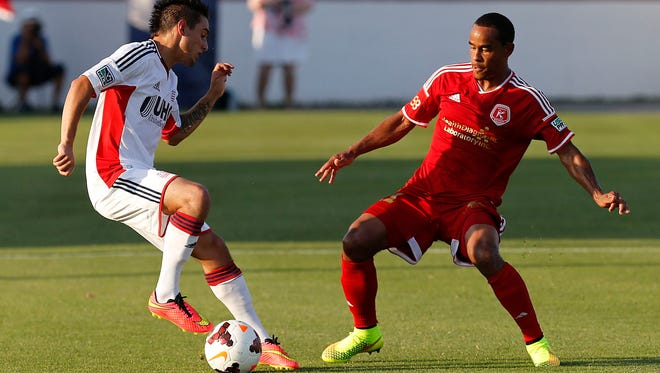 Jun 18, 2014; Richmond, VA, USA; New England Revolution forward Diego Fagundez (14) dribbles the ball as Richmond Kickers midfielder George Davis (11) defends in the first half of the fourth round of the U.S. Open Cup at Richmond City Stadium.