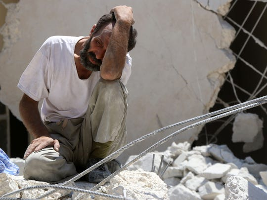 A man looks on as Syrian civil defense workers look