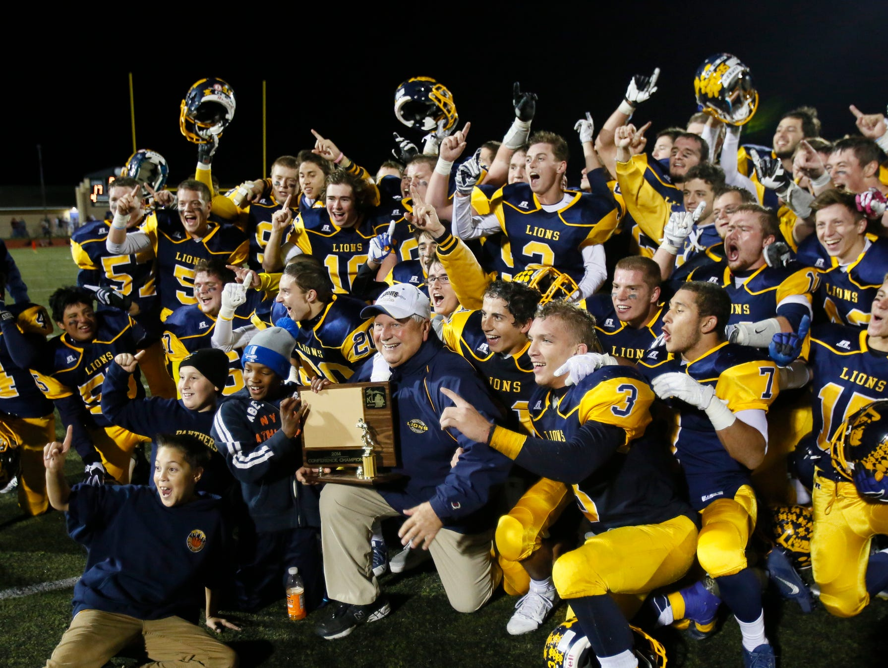 South Lyon coach Mark Thomas holds the district championship trophy as he and his players pose for photos to celebrate their 17-7 win over Canton on Oct. 17, 2014.