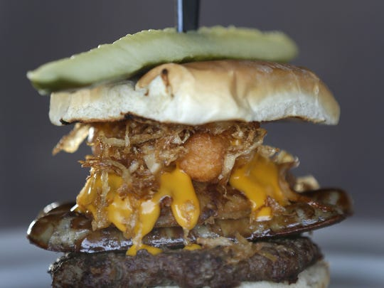 The On Wisconsin Burger gets an upgrade of a beer battered onion ring and fried sauerkraut to go with the burger, sliced brat, fried cheese curds and cheese sauce.