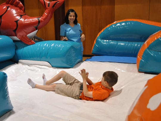 Kids enjoy an inflatable slide Thursday evening during Buddy night at First United Methodist Church in Alexandria.