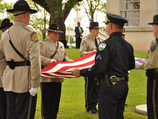 Officers ready an American flag for presentation Friday