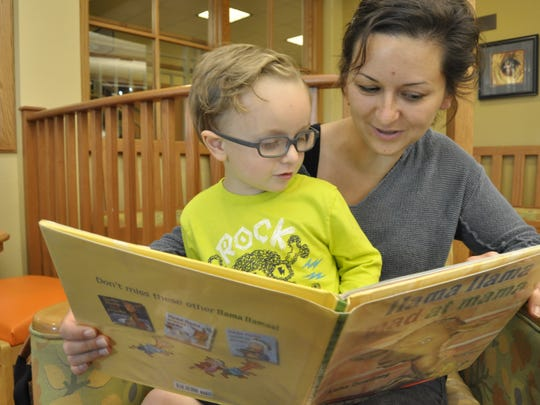 Shandi Childres, right, reads to her two-year-old son Seceda Childres on Monday at the Donald W. Reynolds Library. The library will see a big influx of children and parents as school lets out and parents look for ways to keep their children engaged.