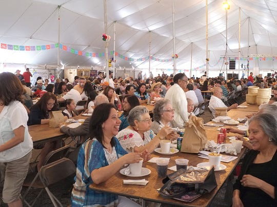 The main tent at the Cristo Rey Fiesta is jammed with people enjoying their lunches.