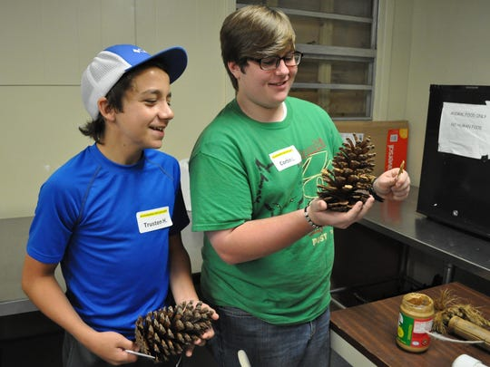 "Trusten Holy (left) and Corbin Loper (right) learn how to make ""enrichment"" items for animals at the Alexandria Zoo while attending a training week for new teen volunteers."