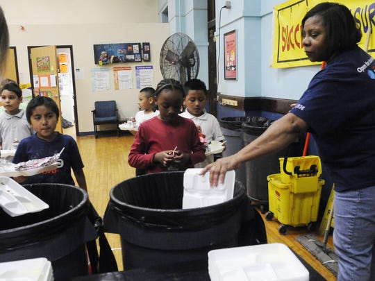Emanuel Gonzalez-Pena, 8, left, and Ezekiel Thomas, 8, center, both second-graders at Clinton Elementary School in the City of Poughkeepsie, throw out what's left of their lunches with the help of Jocye Ashe, right, a cafeteria aide.