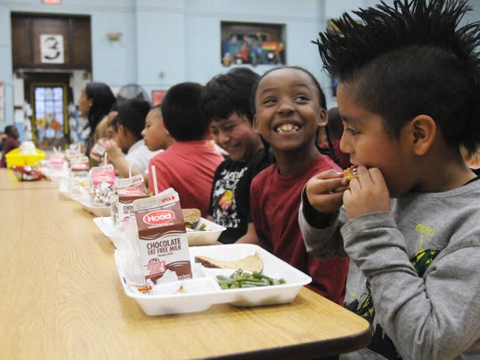 Rickey Martinez, 8, right, and Ezekiel Thomas, 8, center, both second-graders at Clinton Elementary School, eat their lunch in the school cafeteria.