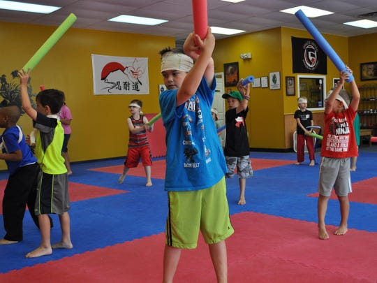 """Pool noodles act as swords for kids during the """"Legos and Lightsabers"""" summer camp."""