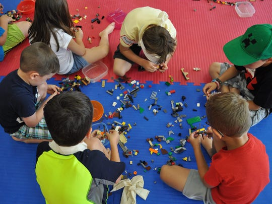 """Kids take a Lego break during the """"Legos and Lightsabers"""" summer camp."""