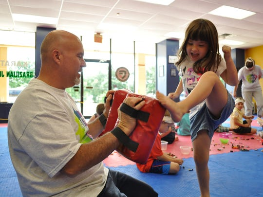 """Clint Duplechian and daughter Harper show of the martial arts moves kids are learning at the """"Legos and Lightsabers"""" summer camp."""