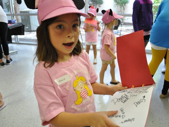 Olivia Dauzat shows off her autographs signed by Disney characters at Princess Boot Camp.