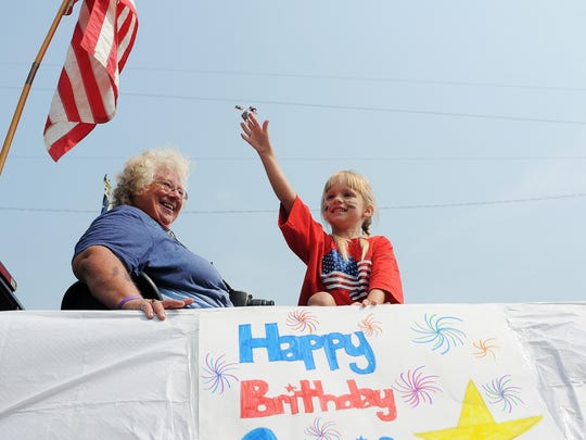 Diane Hoogestraat looks on as her granddaughter Ashley Burgoyn, 5, throws candy to paradegoers during the 4th of July Parade on Saturday, July 4, 2015, in Lennox, S.D.
