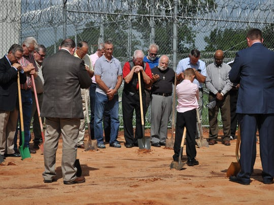 Grant Parish ministers pray before breaking ground for the Grant Parish Detention Center's new chapel on Tuesday.