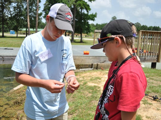 Tyler Carlin (left) helps Caelib Sullivan (right) with his fishing line at the Louisiana Department of Wildlife and Fisheries day camp.