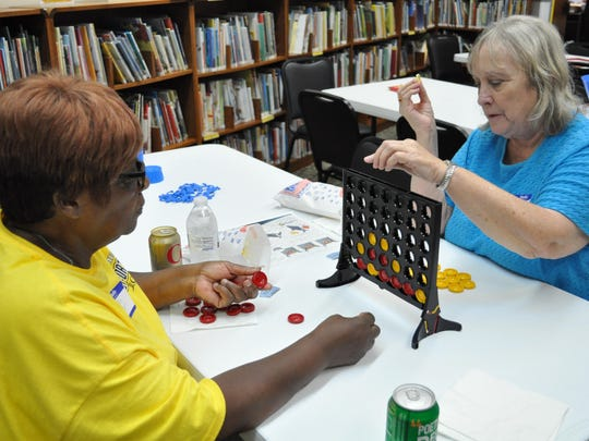 Arthurlene West (left) and Debbie Killian (right) play Connect Four at the Rapides Parish Main Library.