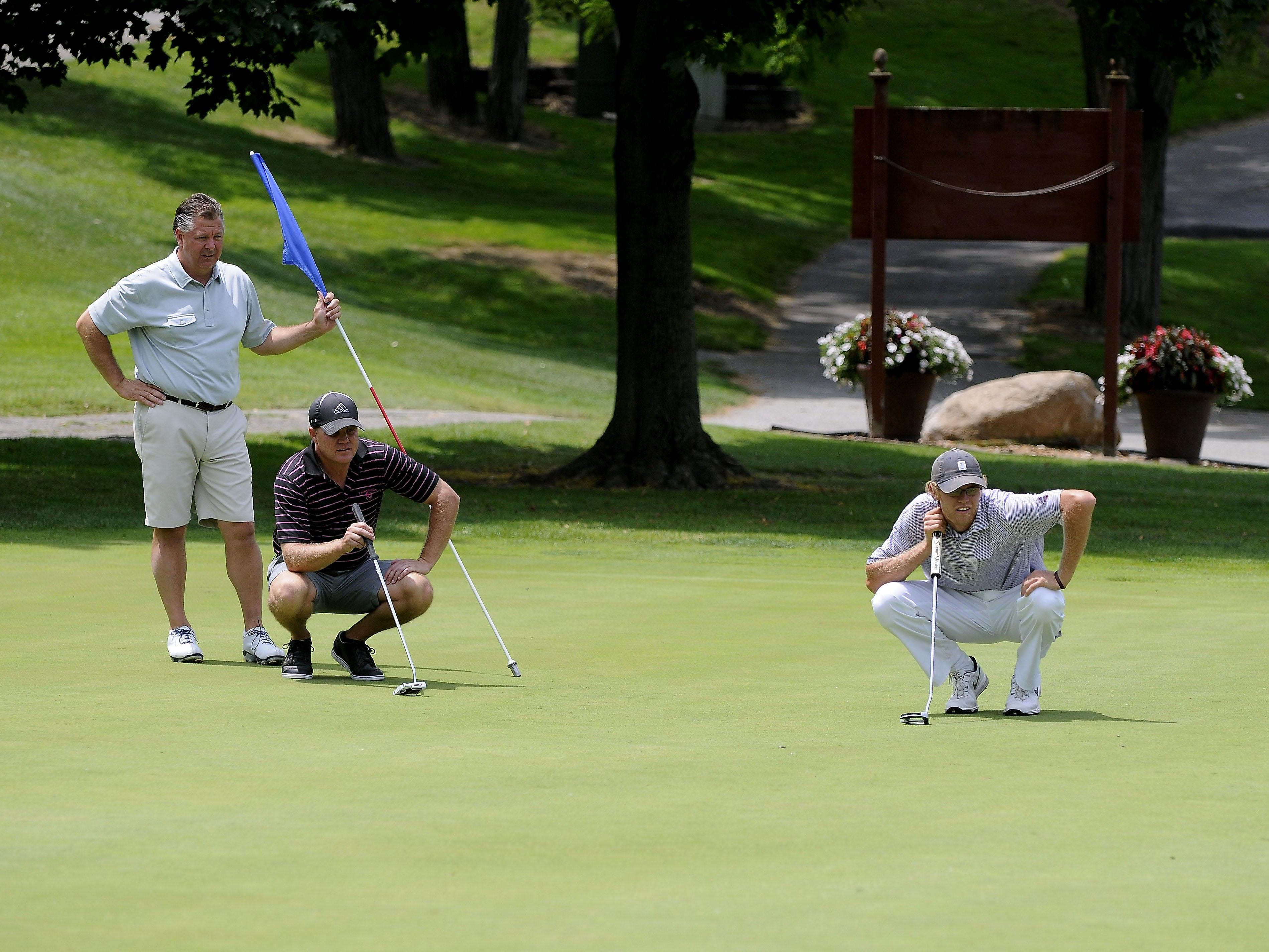 Ted Ernst, Tim Phipps watch as Patrick Cansfield looks over his shot on the 18th green Friday, July 10 during the Port Huron Elks 2015 Men's Invitational in Port Huron Township.