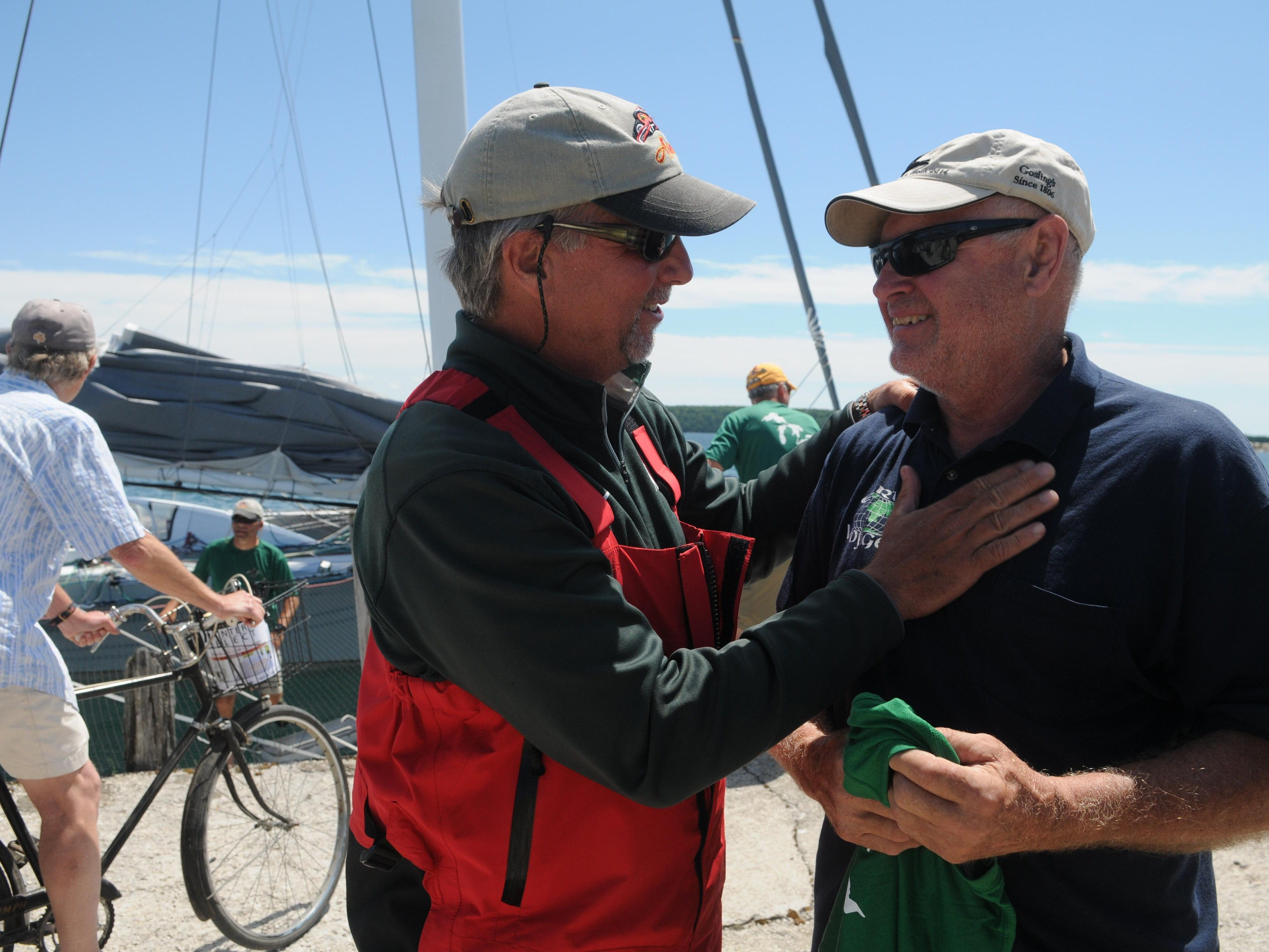 Rick Warner, owner of Arete, talks to Ray Howe, owner of Earth Voyager, after giving him a tee shirt Sunday, July 19, 2015 during the start of the Port Huron-to-Mackinac Island Sailboat Race. Earth Voyager holds the record to the island as a multihull sailboat.