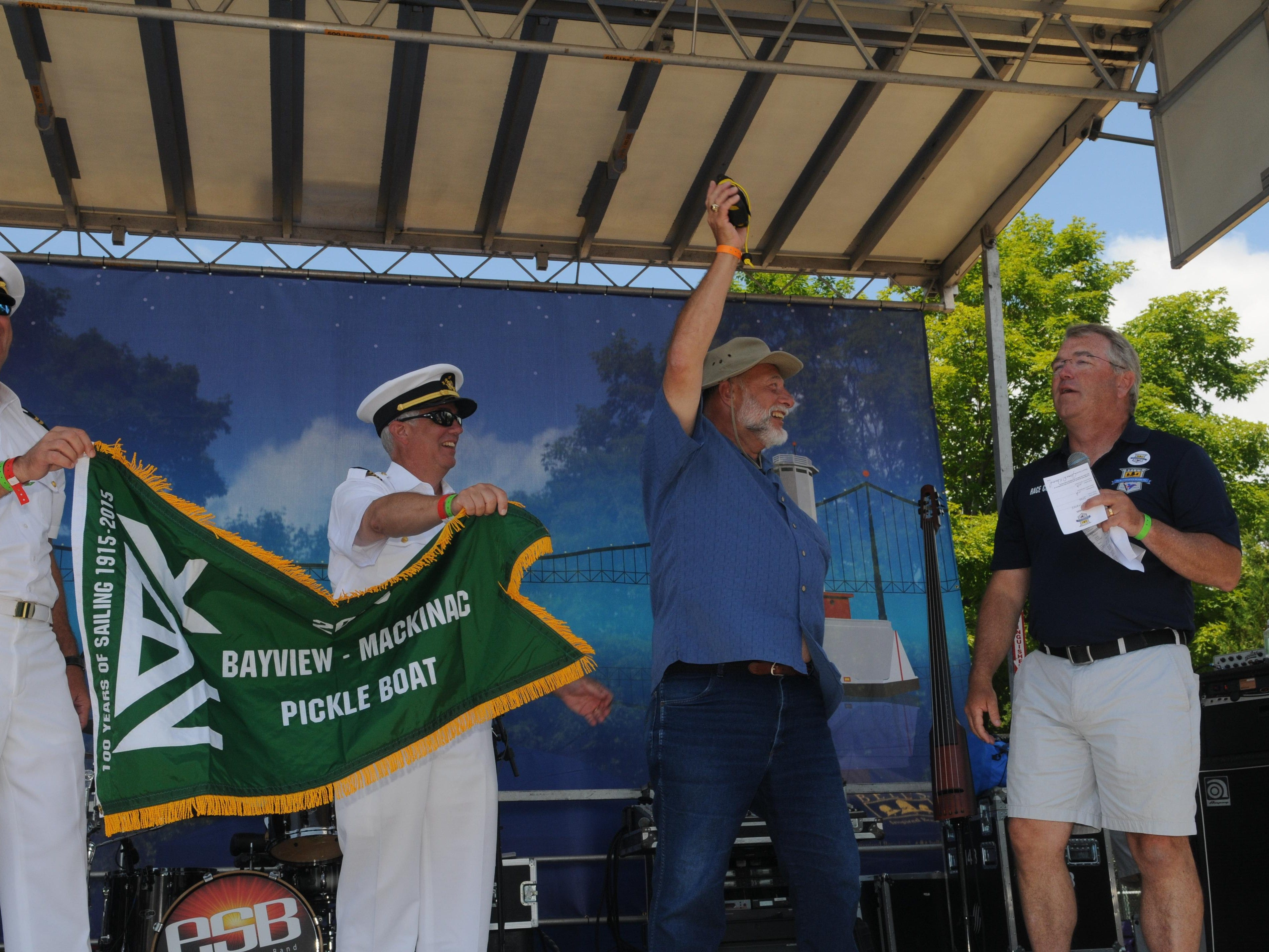 James Howard, of Ark-Imedes, hands over his Yellow Brick tracker to the race officials as he accepts his Pickle Boat pennant for being the last boat to the island Monday, July 20, 2015 during the Port Huron-to-Mackinac Island Sailboat Race. Ark-Imedes is a member of the Bark Shanty Sail Club of Port Sanilac.