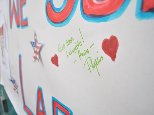 """Messages like this one, """"God Bless Lafayette,"""" fill a banner hung on the side of the Lifeshare Blood Center bus."""