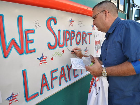 Dwayne Rogers, the director of public safety at Louisiana State University of Alexandria, signs a message of support for the Lafayette community.