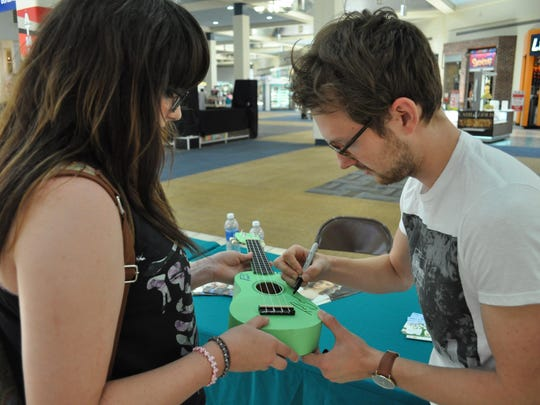 Taylor Mathews autographs a ukulele for Malaina White during a meet and greet at The Alexandria Mall.