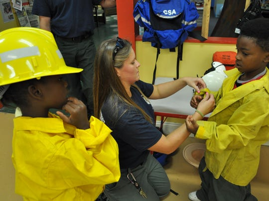 Chandel Conklin, a firefighter with the Kisatchie National Forest, helps Martavious Sanders (left) and Brandon Gilbert (right) try on protective gear during Smokey Bear's birthday party Saturday at the T.R.E.E. House in Alexandria.