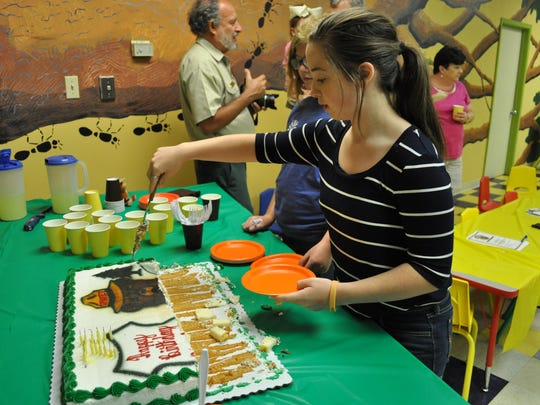 Claire Poleman serves cake during Smokey Bear's birthday party Saturday at the T.R.E.E. House in Alexandria.