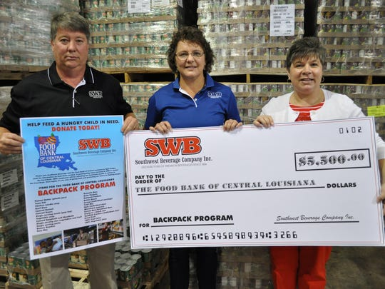 (From left) Dwain Dubroc and Paula Dupuy from Southwest Beverage Company, Inc. present a check to Jayne Wright-Velez, executive director of the Food Bank.