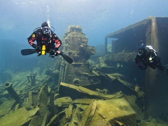 Divers visit the remains of the Nordmeer, a 471-foot German freighter that went down in November 1996 after its crew miscalculated a turn and ran aground. A steel barge rests alongside the wreck, a relic of extensive salvage work.