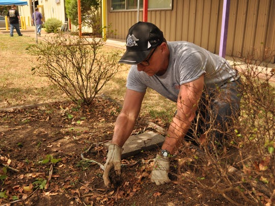 Kelley Pears, a member of the local H.O.G. chapter, spruces up a flower bed Sunday at the T.R.E.E. House Museum.