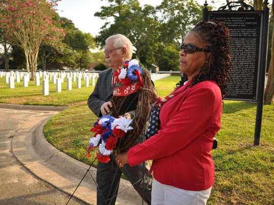 "Peter Henry (left), interim director of the Alexandria Veterans Affairs Health Care System, and Sheila O'Neal-Smith (right), an administrator at the Alexandria National Cemetery, lay the ""Spirit of '45"" wreath by the flagpole located in the middle of the cemetery."