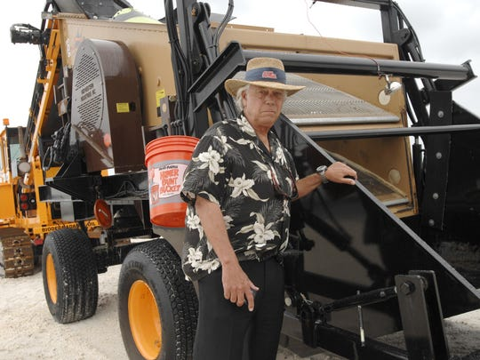 In this 2010 file photo, Santa Rosa Island Authority Executive Director Buck Lee stands next to a Sand Shark, a sand sifting machine that's being used on Pensacola Beach to clean up tar balls and submerged oil. Lee said the beach cleanup ranks as his proudest accomplishment as executive director.